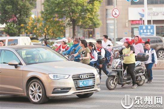 东海大街与东滨路路口无灯控学生过马路穿梭车流中