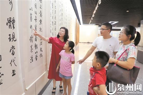 黄鸿琼(左一)为参观者介绍书法艺术