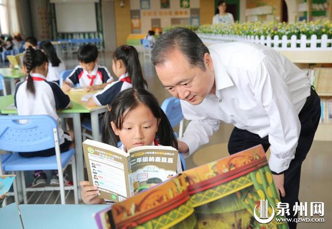 图为在晋光小学东海校区阅览室,市委书记、市人大常委会主任郑新聪俯身查看二年级同学阅读的课外书。陈起拓 摄