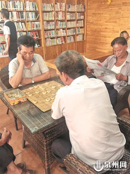 老人们围坐在在一起下棋看报
