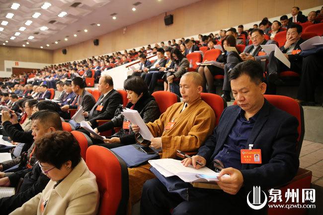 参会人员正在阅读泉州市人民政府工作报告。(陈起拓 摄)