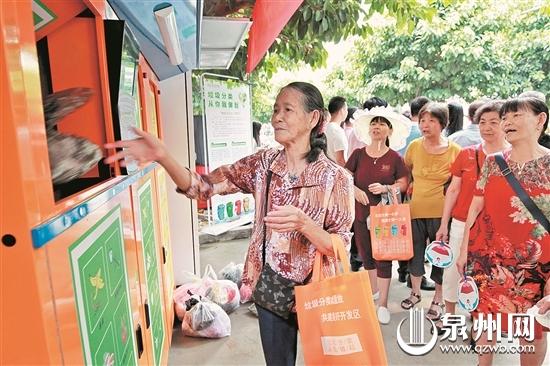 74岁的美华阿婆在垃圾分类督导员的引导下,学着扫码扔垃圾。(陈起拓 摄)